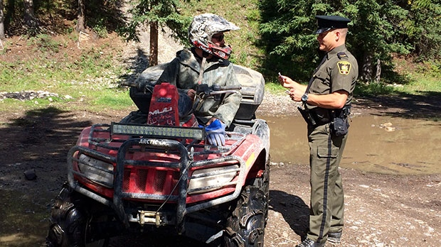 Cochrane District Fish & Wildlife Enforcement officer, Mark Hoskin, checks a quadder's licence and registration as part of increased enforcement in the Ghost Public Use Zone.