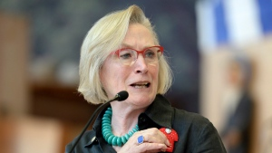 Indigenous Affairs Minister Carolyn Bennett touches a red dress pin symbolizing murdered and missing Indigenous women, as she speaks at the announcement of the inquiry into Murdered and Missing Indigenous Women at the Museum of History in Gatineau, Quebec on Wednesday, Aug. 3, 2016. THE CANADIAN PRESS/Justin Tang