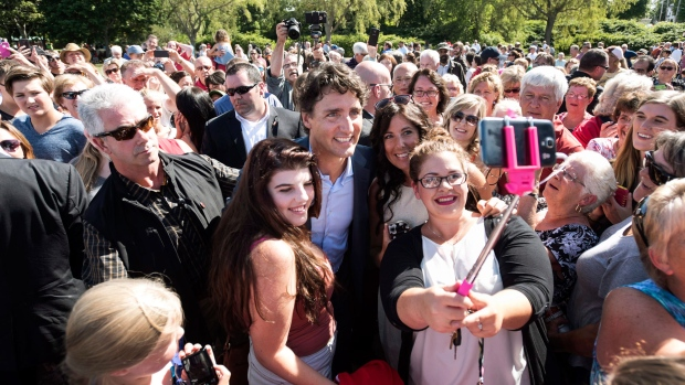 Prime Minister Justin Trudeau poses for selfies with members of the crowd during an event in Bridgetown, N.S. on Tuesday, August 16, 2016. (THE CANADIAN PRESS/Darren Calabrese)