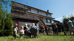 Heather Nyberg along with husband Dan Zimmermann and son Leo and daughter Isabel are seen during a news conference outside their home in Coquitlam, B.C., Friday, August, 5, 2016. The family say they are affected by the B.C. government's new tax on foreign buyers making the sale of their home fall though. (Jonathan Hayward/The Canadian Press)
