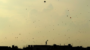 A boy flies a kite from the roof of a house to celebrate Independence Day in New Delhi, India, on Aug. 15, 2013. (Tsering Topgyal / AP)
