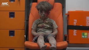 A child sits in an ambulance after being pulled out or a building hit by an airstrike, in Aleppo, Syria on Wednesday, Aug. 17, 2016. (Aleppo Media Center)