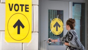 A woman enters Maple High School in Vaughan, Ont., to cast her vote in the Canadian federal election on Monday, Oct. 19, 2015. (Peter Power / THE CANADIAN PRESS)