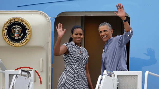 President Barack Obama, right, and first lady Michelle Obama wave as they board Air Force One at the Cape Cod Coast Guard Station in Bourne, Mass., Sunday, Aug. 21, 2016. (AP / Steven Senne)
