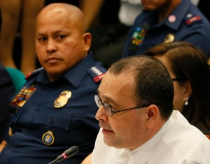 Human Rights Commissioner Chito Gascon, right, gets a stare from Philippine National Police Chief Ronald Dela Rosa as he reads his statement at the start of the Philippine Senate probe on extra judicial killings related to President Rodrigo Duterte's 'War on Drugs' Monday, Aug. 22, 2016 in suburban Pasay city, south of Manila, Philippines.(AP Photo/Bullit Marquez)