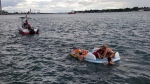 Port Huron Float Down participants climb onto a dinghy on the St. Clair River on Aug. 21, 2016.
