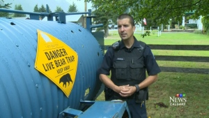 Conservation officer Dan Bartol stands next to a bear trap in Revelstoke, B.C.