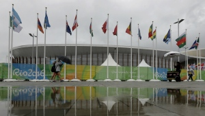 People walk through Olympic Park in the rain at the Rio 2016 games in Rio de Janeiro, Brazil on Aug. 10, 2016 (AP / Charlie Riedel)