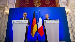 German Interior Minister Thomas de Maiziere, left, and French Interior Minister Bernard Cazeneuve attend a joint media conference in Paris, Tuesday, Aug.23, 2016. (AP Photo/Michel Euler)