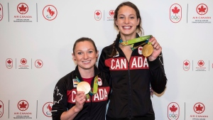 Canada's Olympic gold medallists Penny Oleksiak, right, and Rosie MacLennan pose for media as they are welcomed at the Toronto Pearson Airport in Toronto on Tuesday Aug. 23, 2016. (THE CANADIAN PRESS/Aaron Vincent Elkaim)