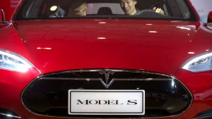 In this Monday, April 25, 2016, file photo, a man sits behind the steering wheel of a Tesla Model S electric car on display at the Beijing International Automotive Exhibition in Beijing. (AP Photo / Mark Schiefelbein, File)