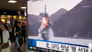 People pass by a TV news program showing a file footage of North Korea's ballistic missile that the North claimed to have launched from underwater, at Seoul Railway station in Seoul, South Korea, Wednesday, Aug. 24, 2016. (AP / Ahn Young-joon)