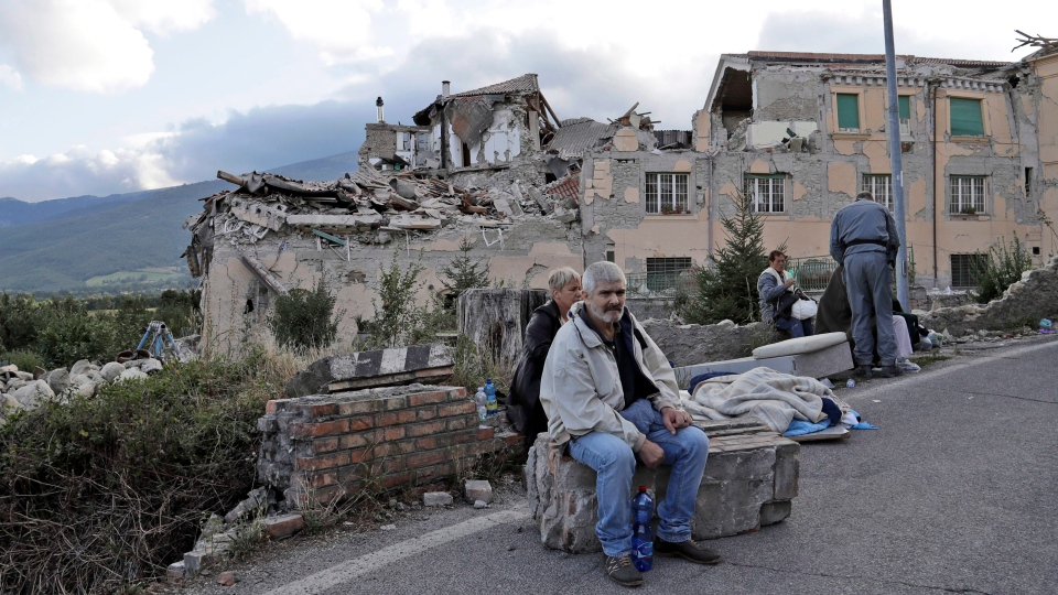People sit on the side of a road as collapsed buildings are seen in the background following an earthquake, in Amatrice, Italy, Wednesday, Aug. 24, 2016. (AP / Alessandra Tarantino)