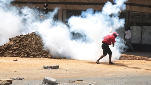 A protestor throws back a teargas canister at police in Harare Wednesday, Aug. 24, 2016, after Zimbabwe police fired tear gas, water cannons and gunshots to stop hundreds of youths protesting against police brutality. (AP Photo)