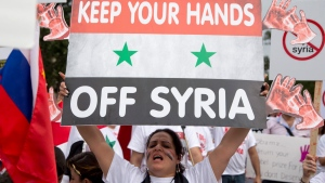 In this Sept. 9, 2013 file photo, protesters against U.S. military action in Syria shout during a demonstration in front of the White House in Washington. (Carolyn Kaster, File/AP Photo)