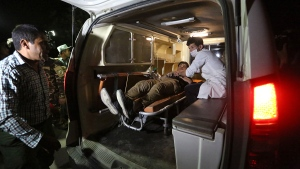 A wounded man is assisted in an ambulance after a complex Taliban attack on the campus of the American University in the Afghan capital Kabul on Wednesday, Aug. 24, 2016. (AP / Rahmat Gul)