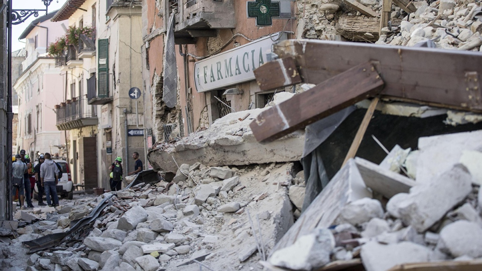 Rescuers stand amidst debris following an earthquake in Amatrice Italy, Wednesday, Aug. 24, 2016. (Massimo Percossi / ANSA via AP)