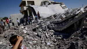 Syrians gather by the rubble of a house, destroyed from Syrian forces shelling, in the Syrian town of Azaz, on the outskirts of Aleppo, Syria in this Monday, Sept. 3, 2012 file photo. (Muhammed Muheisen/AP)