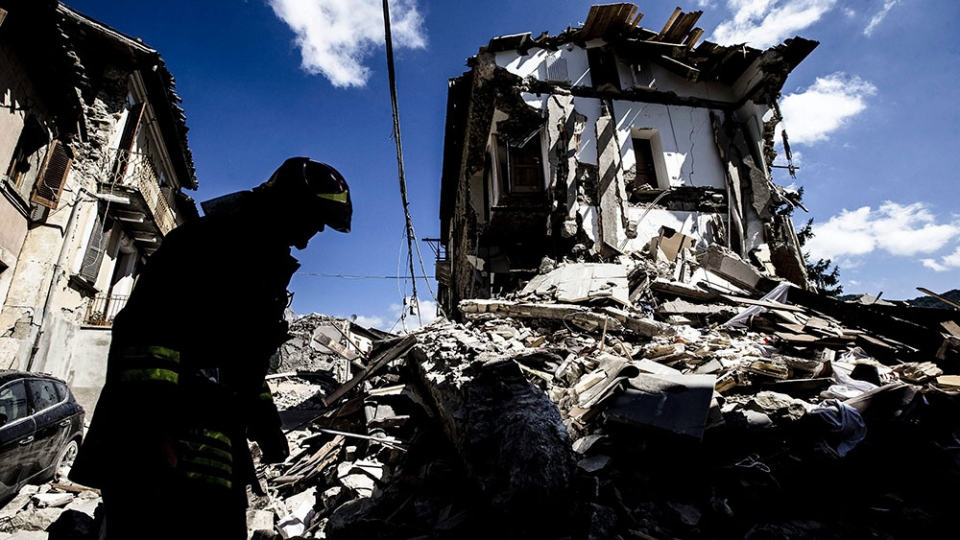 A firefighter inspects a collapsed house in Arquata, central Italy, Thursday, Aug. 25, 2016. (Angelo Carconi/ANSA)