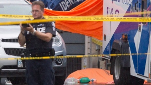 A body lies covered in front of a house in Scarborough, Ont., on Thursday, August 25, 2016, after three people were killed in a crossbow attack. THE CANADIAN PRESS/Chris Young