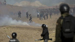 Independent miners clash with the police as they run from clouds of tear gas during protests in Panduro, Bolivia on Thursday, Aug. 25, 2016. (AP / Juan Karita)