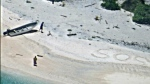 "A pair of stranded mariners signal for help by writing ""SOS"" in the sand as a U.S. Navy P-8A Poseidon aircraft crew from Patrol Squadron (VP) 8 flies over in support of a Coast Guard search and rescue mission. (U.S. Navy / Handout)"