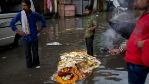 A dead body lies in a flooded street Friday, Aug. 26, 2016 before a Hindu funeral at the Harishchandra Ghat in Varanasi, India. A flood of the Ganges River this week following heavy monsoon rains kept away thousands of Hindu devotees from the holy cremation site. (Tsering Topgyal/ THE ASSOCIATED PRESS)