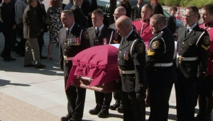 Pallbearers carry the casket of Mauril Belanger into Notre-Dame Cathedral.