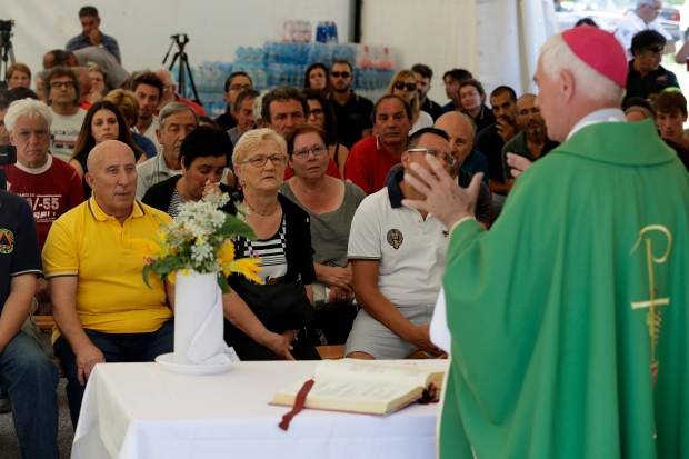 The bishop of Ascoli Piceno, Giovanni D'Ercole, celebrates mass in a tent camp set in Pescara del Tronto, near Amatrice, central Italy, Sunday, Aug. 28, 2016. (AP / Andrew Medichini)