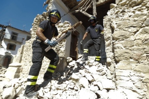 Firefighters retrive a crucifix from a church in the small town of Rio, near Amatrice, central Italy, Sunday, Aug. 28, 2016. (AP Photo/Andrew Medichini)
