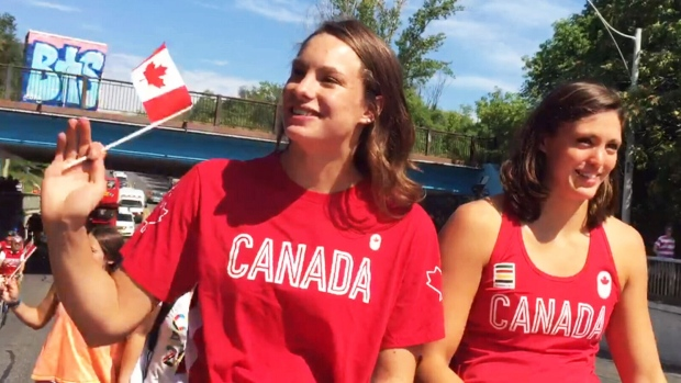 Swimmers Penny Oleksiak, left, and Michelle Williams take in the crowds at a parade in honour of Canada's athletes Sunday in Toronto.