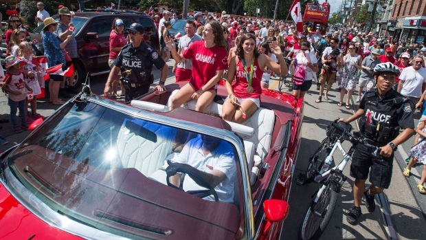 Canada's Rio Games team flag-bearer and gold medalist Penny Oleksiak and fellow swim team member Michelle Williams ride in the back of a parade car for an Rio 2016 Games parade celebration in Toronto on Sunday August 28, 2016. THE CANADIAN PRESS/Aaron Vincent Elkaim