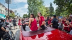 Canada's Olympic team flag-bearer and gold medalist Penny Oleksiak, centre right, and fellow swim team member Michelle Williams ride in the back of a prade car for an Olympic parade celebration in Toronto on Sunday August 28, 2016. THE CANADIAN PRESS/Aaron Vincent Elkaim