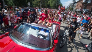 Team Canada's flag-bearer and gold medalist Penny Oleksiak and fellow swim team member Michelle Williams ride in the back of a prade car for a Rio 2016 parade celebration in Toronto on Sunday August 28, 2016. (Aaron Vincent Elkaim / THE CANADIAN PRESS)