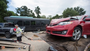 Tow truck operator Lee Maguire helps clean up the scene of a fatal wreck on Interstate 10 near Laplace on Sunday, Aug. 28, 2016. A bus full of construction workers, seen, hit a firetruck on an elevated highway Sunday, killing a few people and injuring dozens, several of them seriously, Louisiana State Police said. (Chris Granger/NOLA.com The Times-Picayune via AP)