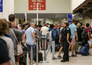 A police officer stands guard as passengers wait in line at Terminal 7 in Los Angeles International Airport, Sunday, Aug. 28, 2016. (AP Photo/Ringo H.W. Chiu)