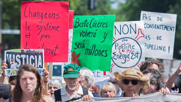 Protesters hold up signs during a protest to highlight environmental and social issues in Montreal, Thursday, August 11, 2016. (Graham Hughes/The Canadian Press)