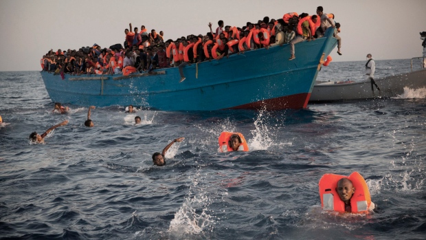 Migrants, most of them from Eritrea, jump into the water from a crowded wooden boat as they are helped by members of an NGO during a rescue operation at the Mediterranean sea, about 20 km north of Sabratha, Libya, Monday, Aug. 29, 2016. (Emilio Morenatti/AP)