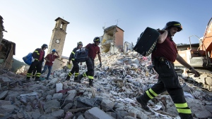 Firefighters carry personal belongings retrieved from houses, in Amatrice, central Italy, Monday, Aug. 29, 2016. (Massimo Percossi / ANSA via AP)