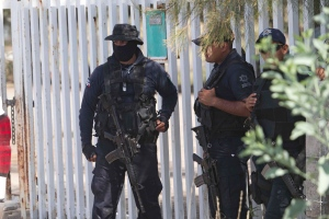 In this May 22, 2015, file photo, Mexican state police stand guard near the entrance of Rancho del Sol, near Vista Hermosa, Mexico. (AP Photo/Refugio Ruiz)