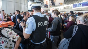 A policeman talks to people in the departure area at Frankfurt airport, central Germany, Wednesday, Aug. 31, 2016. (Frank Rumpenhorst/dpa via AP)