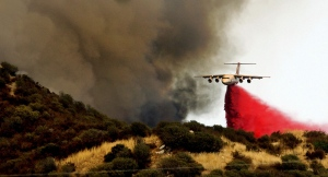 A jet tanker dumps retardant on the hillside above homes to block the southern movement of a wildfire as it burns near homes in the brush in Beaumont, Calif., Tuesday, Aug. 30, 2016. (Terry Pierson/The Press-Enterprise via AP)