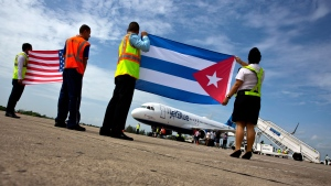 Airport workers receive the JetBlue flight 387 holding a United States, and Cuban national flag, on the airport tarmac in Santa Clara, Cuba, Wednesday, Aug. 31, 2016. (Ramon Espinosa/AP Photo)