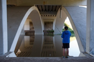 Brasil Robalo, 11, fishes under an overpass as water levels of the North Saskatchewan River rise in Edmonton, Alta., on Wednesday, Aug. 24, 2016. (THE CANADIAN PRESS / Codie McLachlan)