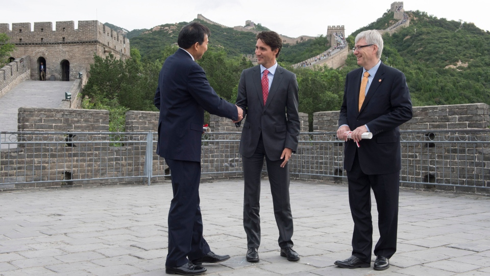 Prime Minister Justin Trudeau shakes the hand of Chinese Ambassador to Canada Luo Zhaohui as Canadian Ambassador to China Guy Saint-Jacques looks on following an exchange of documents atop a section of the Great Wall of China, in Beijing on Thursday, Sept. 1, 2016. (Adrian Wyld / THE CANADIAN PRESS)