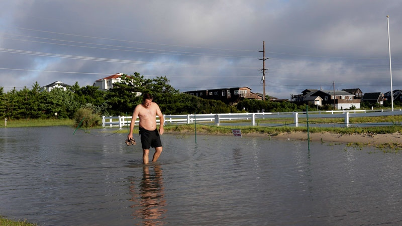 Paul O'Brien checks the depth of the road near the home he rented for vacation in Rodanthe, N.C., Saturday, Sept. 3, 2016 after Tropical Storm Hermine passed the Outer Banks. (AP /Tom Copeland)