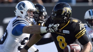 Toronto Argonauts' Daryl Waud (99) reaches for the mask of Hamilton Tiger-Cats' Jeremiah Masoli (8) for a major foul during first half CFL Eastern Division Semifinal football action, in Hamilton, Ont., on Sunday, Nov. 15, 2015. (Frank Gunn/The Canadian Press)