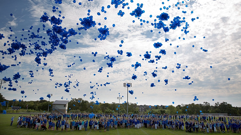 In this Saturday, Sept. 3, 2016, photo, community members release blue balloons while standing in the formation of a heart during a Love for Lane Celebration on what would have been Lane Graves' third birthday, in Omaha, Neb. (Rebecca S. Gratz / Omaha World-Herald via AP)