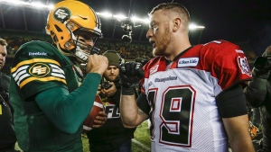 Calgary Stampeders quarterback Bo Levi Mitchell, right, and Edmonton Eskimos quarterback Mike Reilly embrace following the CFL West Division final in Edmonton, on Sunday, Nov. 22, 2015. Labour Day's Battle of Alberta in the CFL will showcase of the top two quarterbacks in the league. (THE CANADIAN PRESS/Jeff McIntosh)