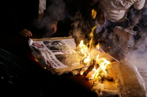 Demonstrators burn a poster with a photo of Brazil's President Michel Temer during a protest in Sao Paulo, Brazil, Sunday, Sept. 4, 2016. Temer was sworn in as Brazil's new leader on Wednesday following the ouster of Dilma Rousseff. (AP Photo/Nelson Antoine)